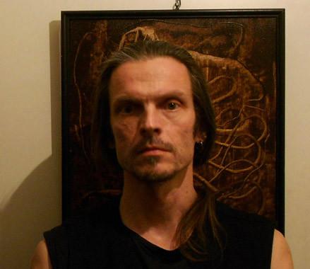 Valokuva. Taiteilija Vuha Vuorma seisoo maalauksensa edessä.
